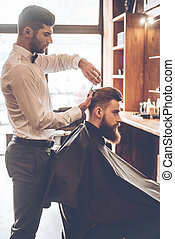 Barber at work. Side view of young bearded man getting haircut by hairdresser while sitting in chair at barbershop