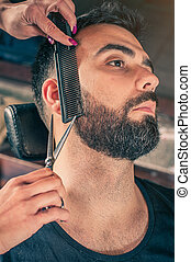 Barber beard cut a client's beard with clippers - Female...
