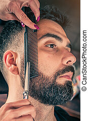 Barber beard cut a client's beard with clippers