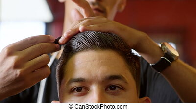 Barber combing customer hair at barber shop 4k - Close-up of...