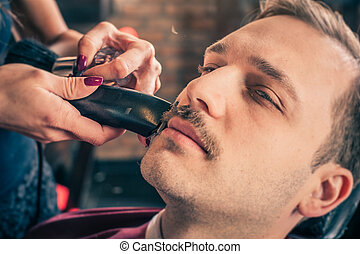 Barber cut a client's mustache with trimmer