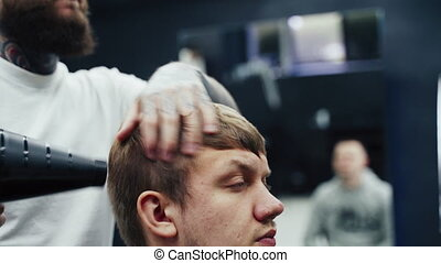 Barber drying male hair in hairdressing salon. Handheld shot...