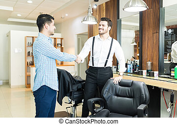 Barber Greeting Customer With A Handshake In Shop