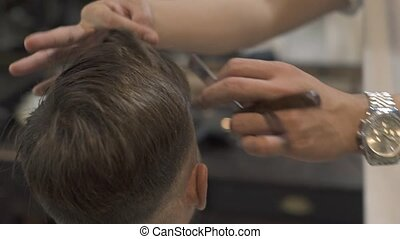 Barber haircut with shaving razor in male salon. Hairstylist using straight razor for shave hair. Close up hairdresser shaving hair in hairdressing salon. Male hairdo concept.