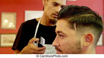 Barber interacting with man while cutting his hairs 4k -...