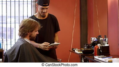 Barber interacting with man while using digital tablet 4k -...