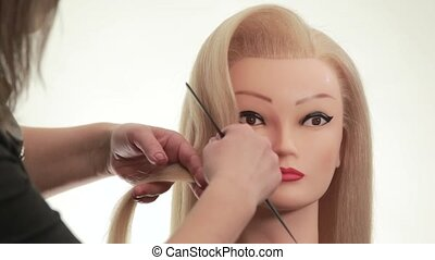 Master using the spray for fixing hair and comb makes a wave out of the hair, barber shows the variant hairstyles for long hair, on white background, close up