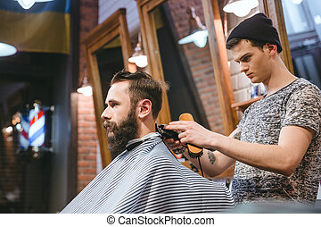 Barber making haircut to handsome man with beard - Barber...