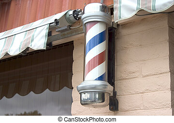 A barber pole outside of a hair salon.