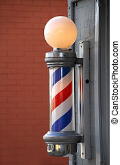 A barber Pole outside of old barber shop in a small town