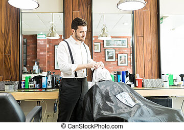 Barber Putting Warm Towel On Man's Face In Salon