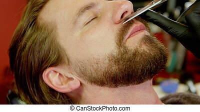 Barber setting mans beard in barbershop 4k - Close up of...