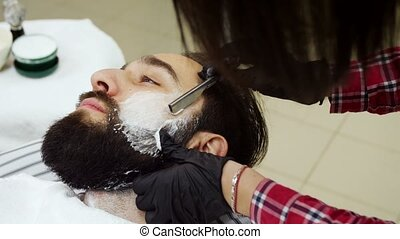 Barber shaves a white man with a straight razor