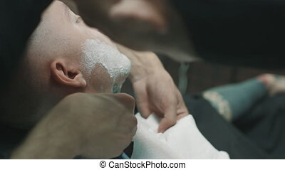 Barber shaves the beard of the client.