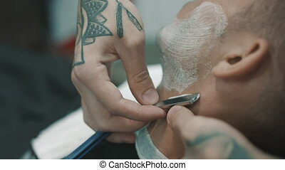 Barber shaves the beard of the client. - Shaves the beard....