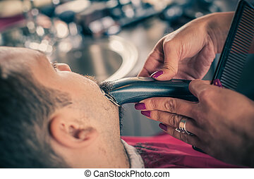 Barber shaving a client with trimmer