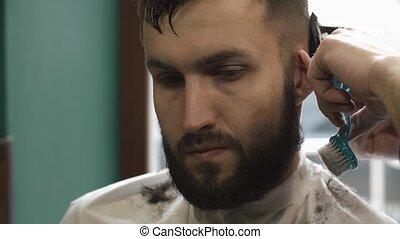 Barber shaving the hair in the barbershop.