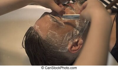 Barber shaving with straight razor to bearded man in male salon. Close up shaving beard with straight razor and soap foam on face. Barbershop concept. Male beard care