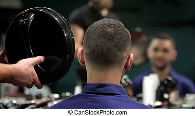 Barber shows short haircut with mirror