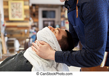barber softening male face sking with hot towel