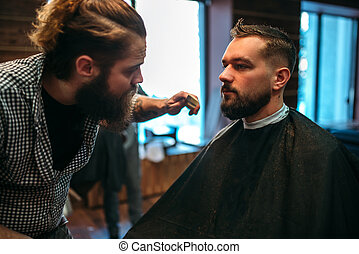 Barber styling mustache and beard at barbershop