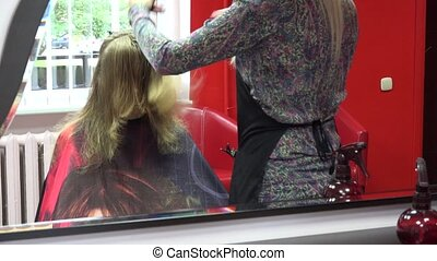 barber stylist comb and trim female customer hair in front...