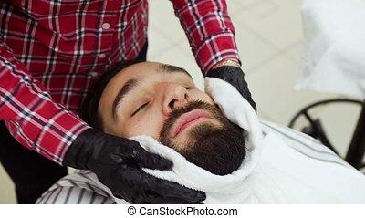 Barber towel wipes his beard