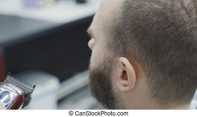 Barber trimming bearded man with shaving machine in ...