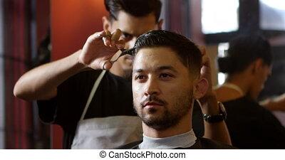 Barber trimming clients hair at barber shop 4k