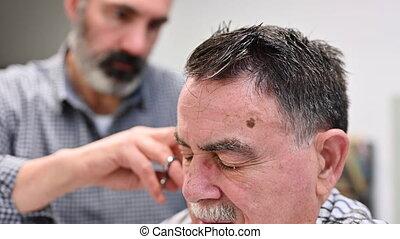 Barber trimming hair of old man at barber shop.