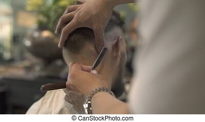 Barber using shaving razor in male salon. Hairdresser shave hair on nape with straight razor in barbershop. Close up hairdresser shaving hair in hairdressing salon. Hipster hairstyle concept.