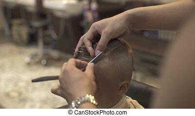 Barber using straight razor for shaving hair on head of little boy in hairdressing salon. Close up shaving hair with retro razor in barbershop. Children cutting and boy hairstyle.