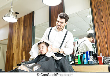 Barber Wiping Head Of Boy With Towel In Salon
