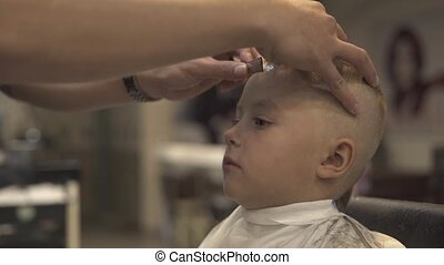 Barber with shaving razor doing boy hairstyle in male salon. Childen hairstyle concept. Hairdresser using straight razor for shave hair little boy. Hairstylist doing boy hairdo in hairdressing salon.