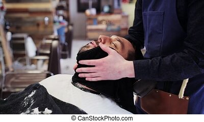barber with towel cleaning male face after shaving
