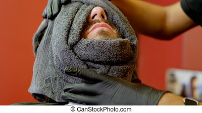 Barber wrapping mans face in hot towel 4k - Barber wrapping...