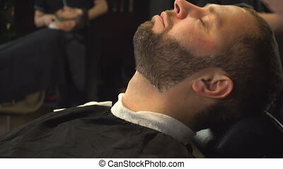 Barberman shaving beard of man