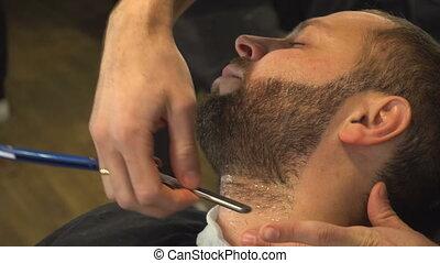 Barberman shaving beard of man - Barberman in barber shop...