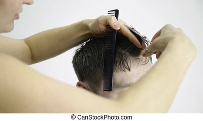 barbers hands uses scissors for shaping mens hair in a...
