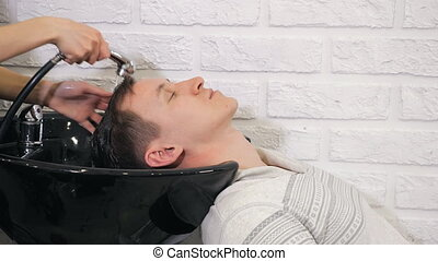 Barbershop, hairdresser washes the head of a man, 4k