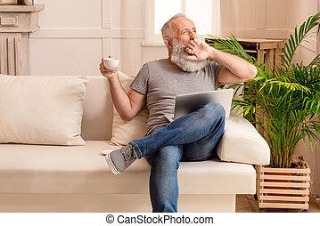 barbuto, sbadigliare, seduta, divano, laptop, tazza, caffè, mentre, casa, uomo senior
