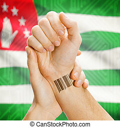 Barcode ID number on wrist and national flag on background - Abkhazia
