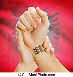Barcode ID number on wrist and national flag on background - Albania