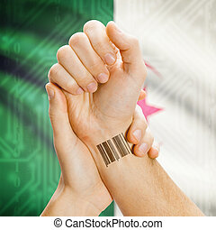 Barcode ID number on wrist and national flag on background - Algeria