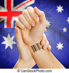 Barcode ID number on wrist and national flag on background - Australia