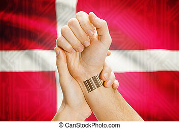 Barcode ID number on wrist of a human and national flag on background - Denmark