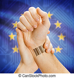 Barcode ID number on wrist of a human and national flag on background - European Union