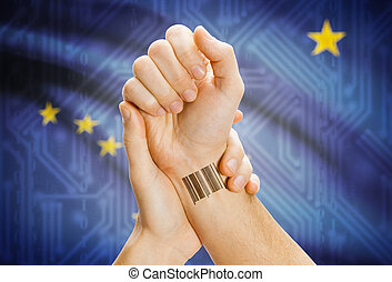 Barcode ID number on wrist and USA states flags on background - Alaska