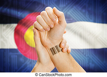 Barcode ID number on wrist and USA states flags on background - Colorado