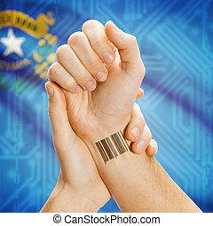 Barcode ID number tatoo on wrist and USA statesl flag on background - Nevada